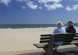 Older folks sitting on bench near the ocean